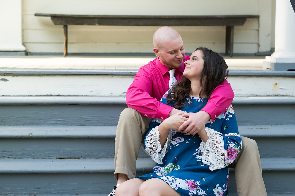 Engaged couple sitting on gray stairs at Bethany College during their engagement photo session.