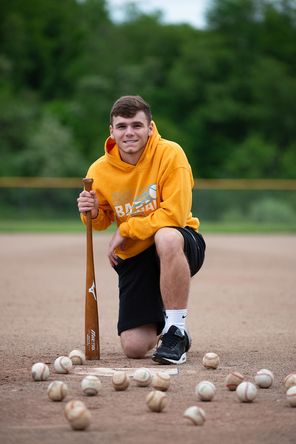 Senior guy kneeling on baseball field holding his bat and surrounded by baseballs during his photoshoot