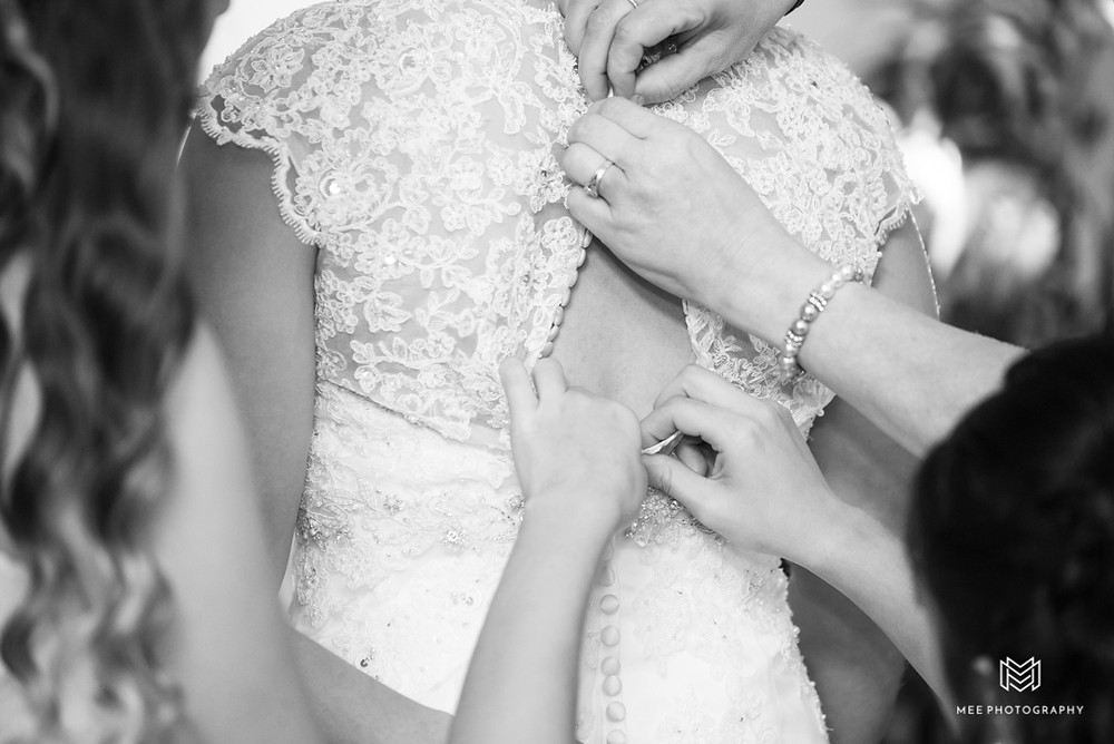 Black and white photo of bride getting in her dress