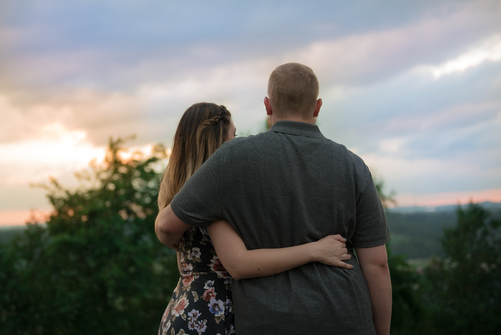 A couple holding each other and watching the sunset during their Morgantown engagement session