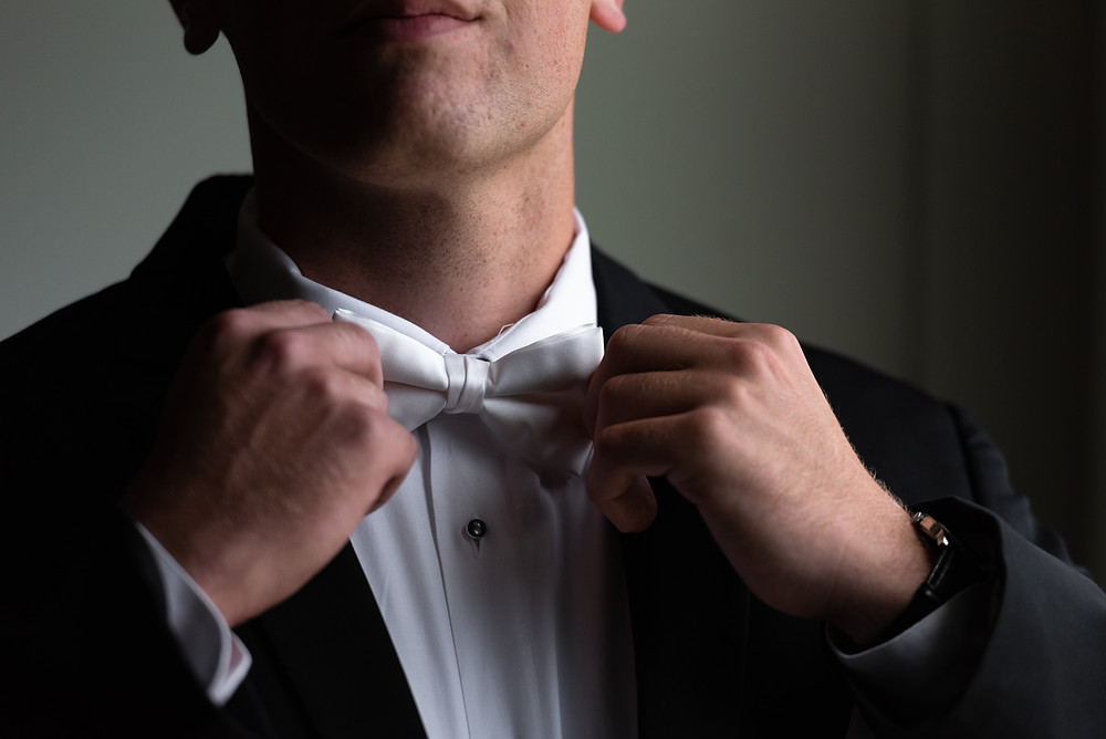 Groom fixing his bow tie before the ceremony at Heinz Chapel