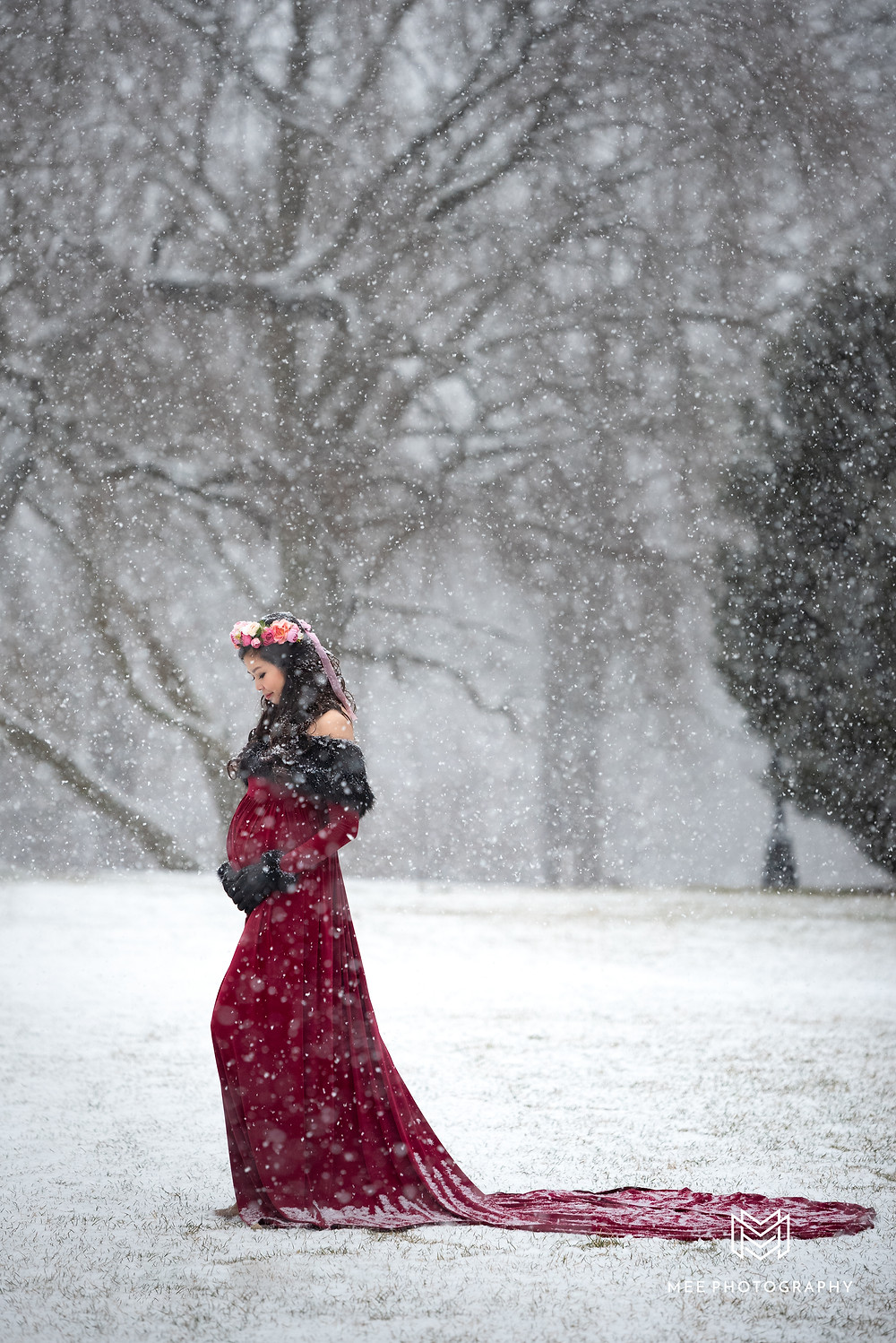 Woman wearing red maternity dress with train in the snow at Hartwood Acres near Pittsburgh