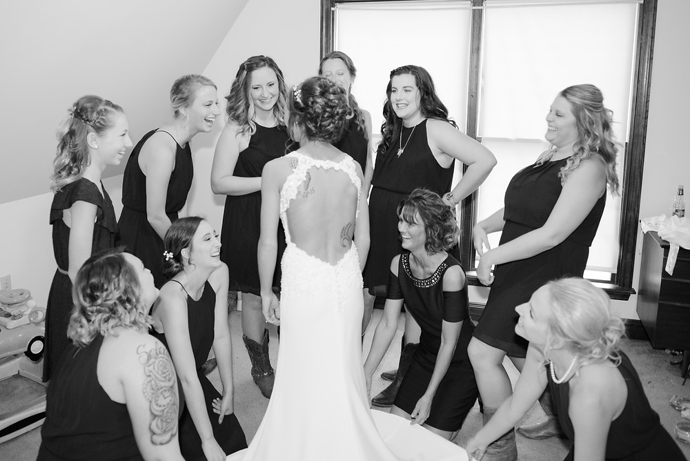 A black and white photograph of the bridesmaids helping the bride get ready before the wedding.