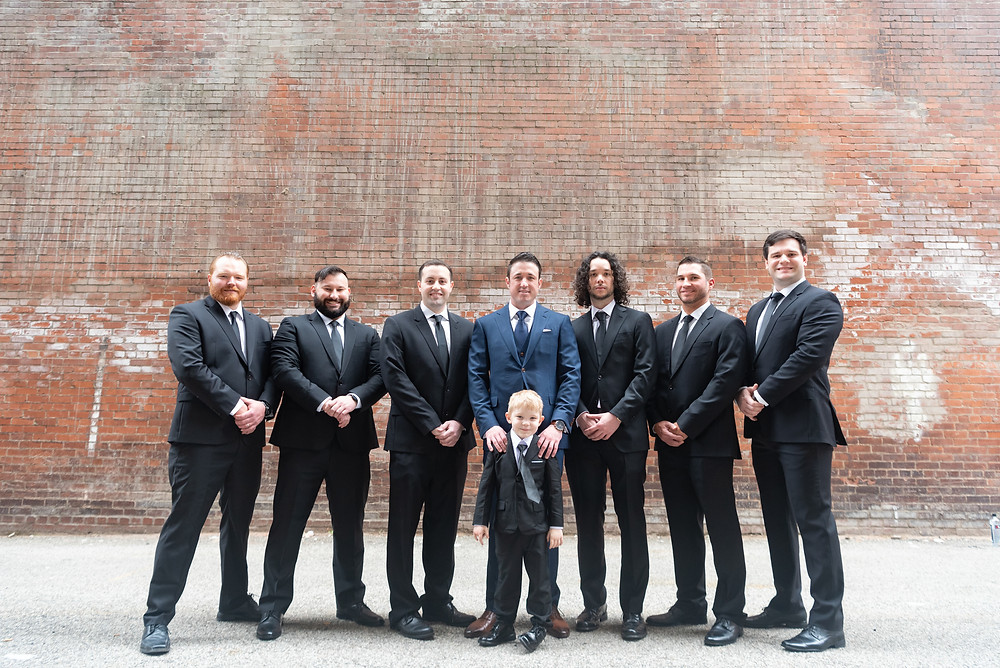 Groomsmen posed in front of a brick wall during photos in Pittsburgh