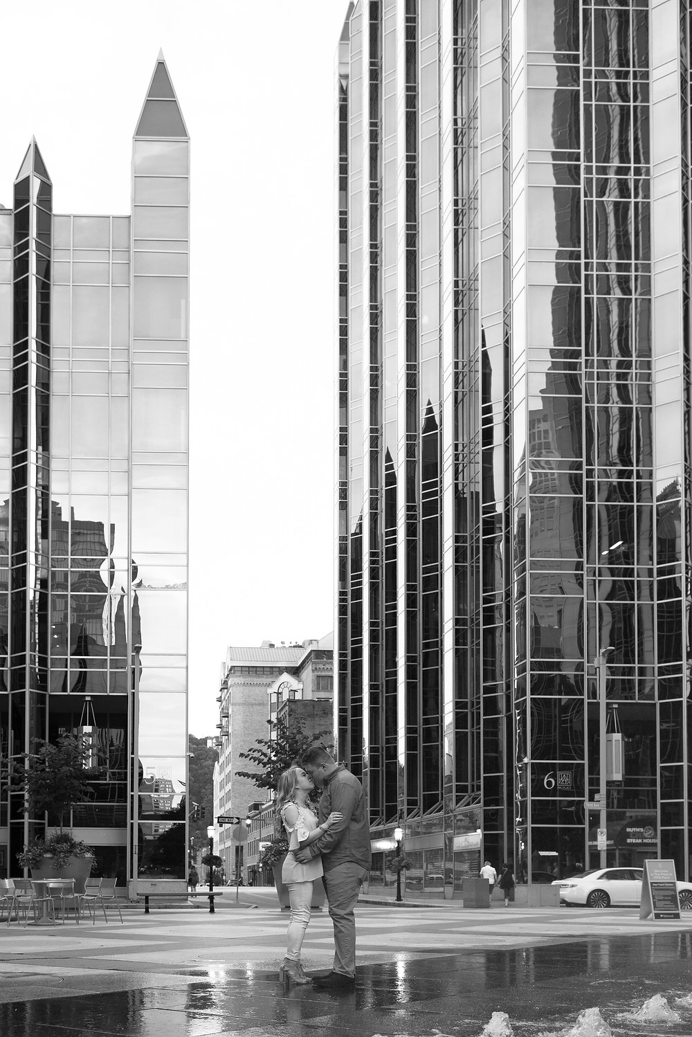 A black and white photograph of PPG Place towering over the couple during their engagement session.