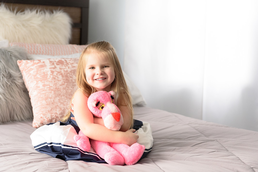 Four year old girl posed sitting on a bed holding a pink panther and smiling at the camera.