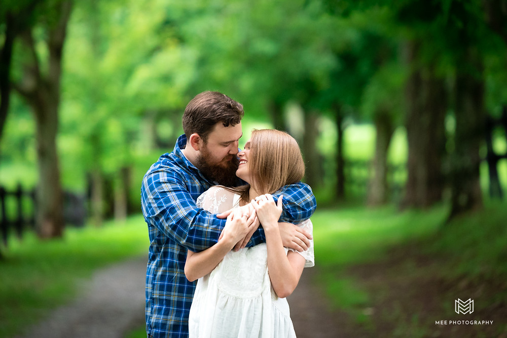 Guy posed with his arms around his fiance during their country engagement shoot.