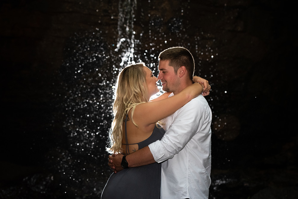Engagement session in front of a waterfall at night at Tomlinson Run State Park