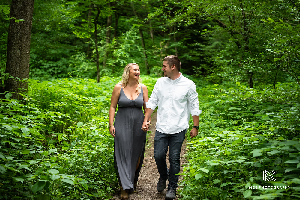 Couple walking and holding hands in the woods at Raccoon Creek State Park