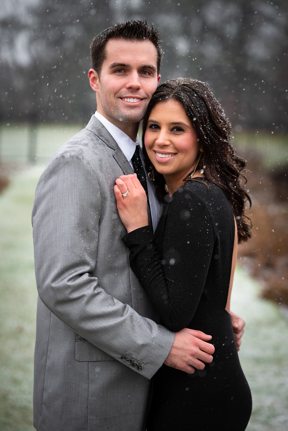 Couples portraits with girl wearing a black gown and guy wearing a gray suit