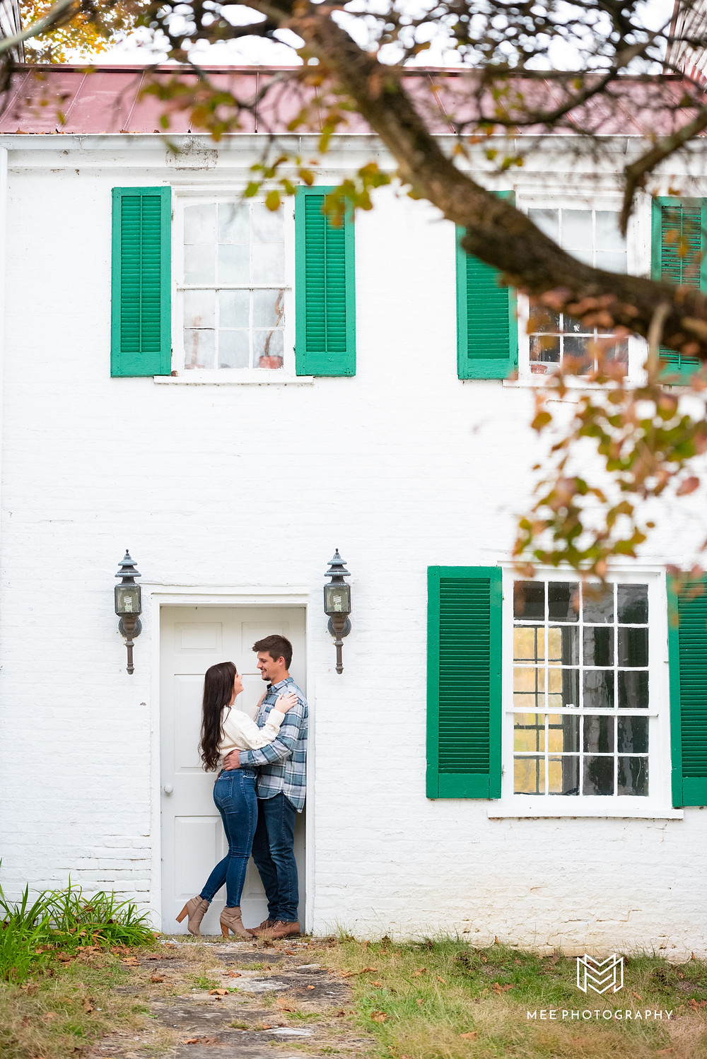 Bethany College fall engagement session in front of a white farmhouse with green shutters