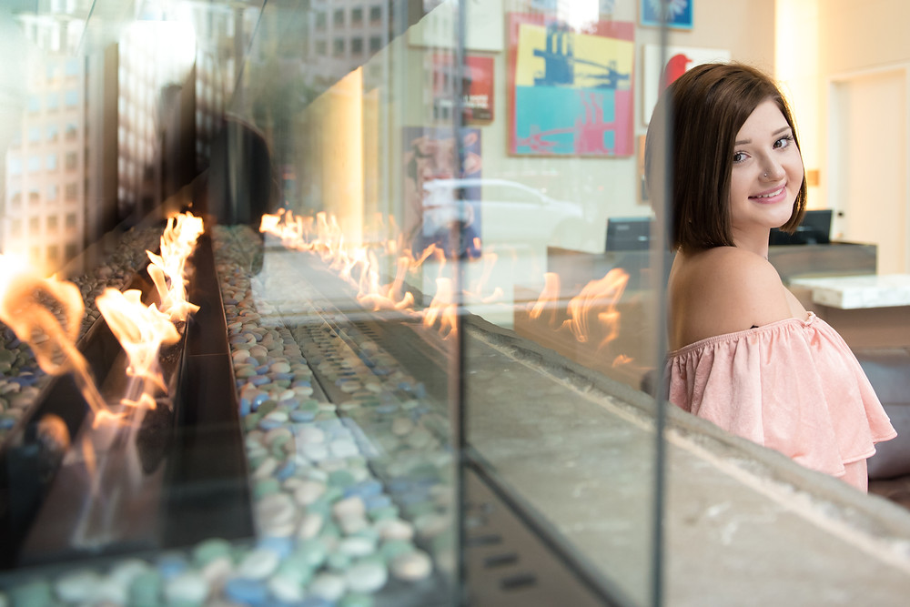High school female in front of the fireplace at the Fairmont Hotel in Pittsburgh. She is smiling at the camera in a pink dress.