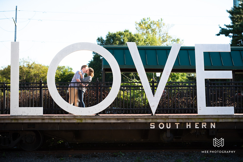 Couple kissing in front of the love sign in Manassas, Virginia during their engagement shoot.