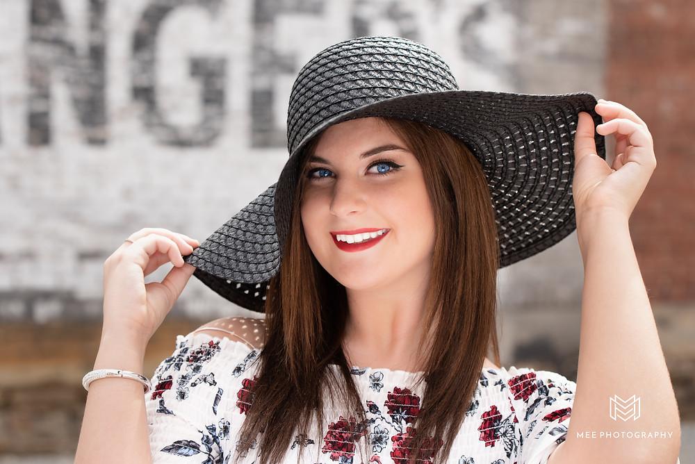 Senior girl posed holding black floppy hat on her head during her senior pics in East Liverpool, OH