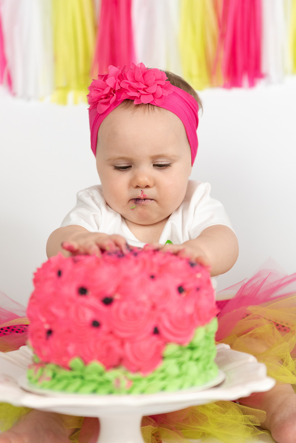 One year old girl diggin into her smash cake during photoshoot