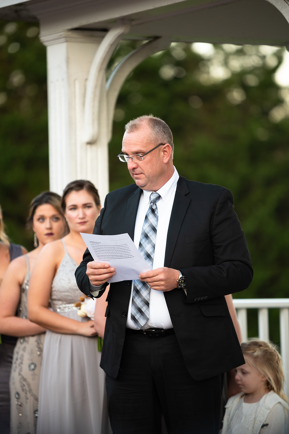 A family friend giving a speech during a chilly outdoor wedding ceremony in Maryland