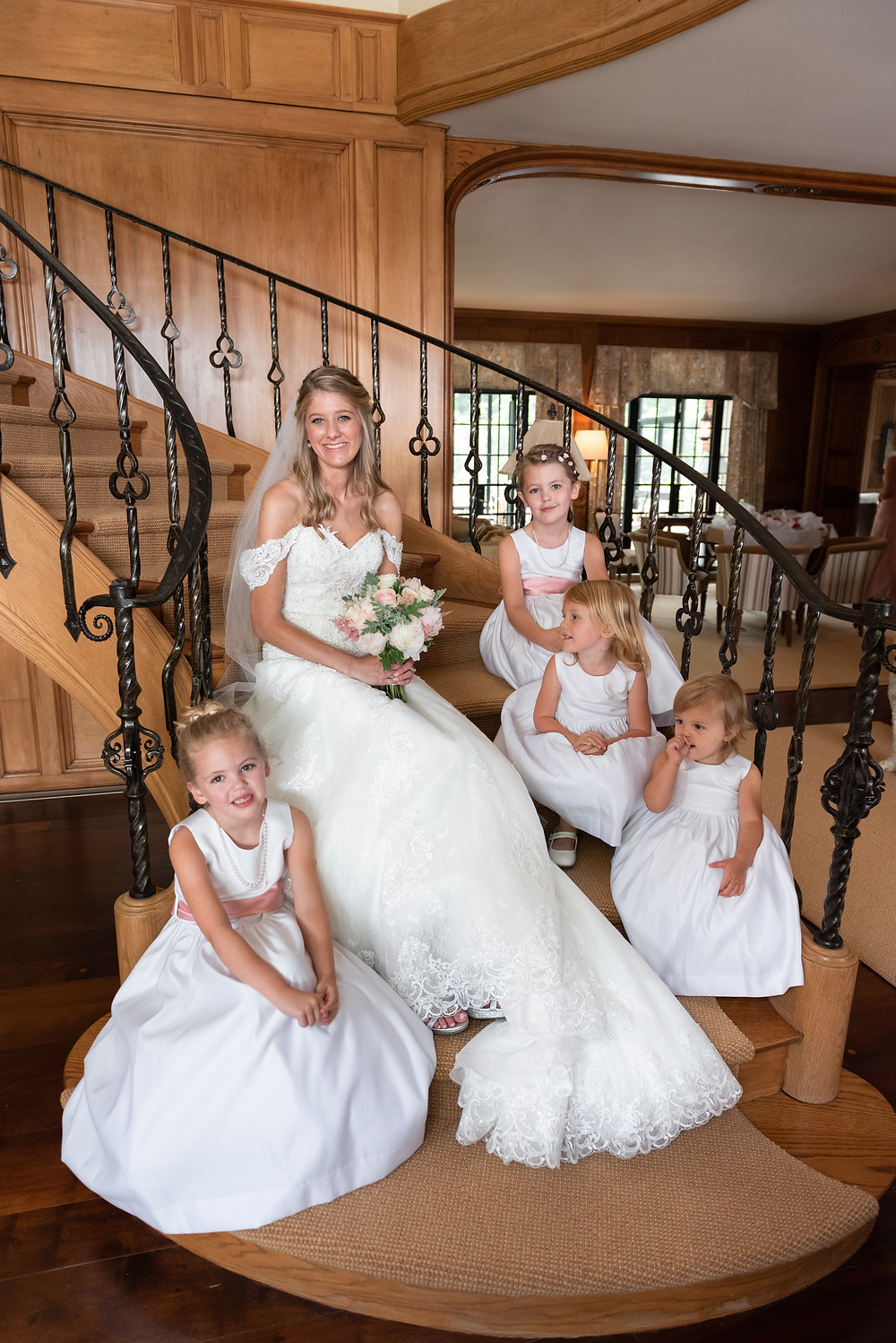 Bride sitting on spiral staircase with flower girls before their estate wedding ceremony