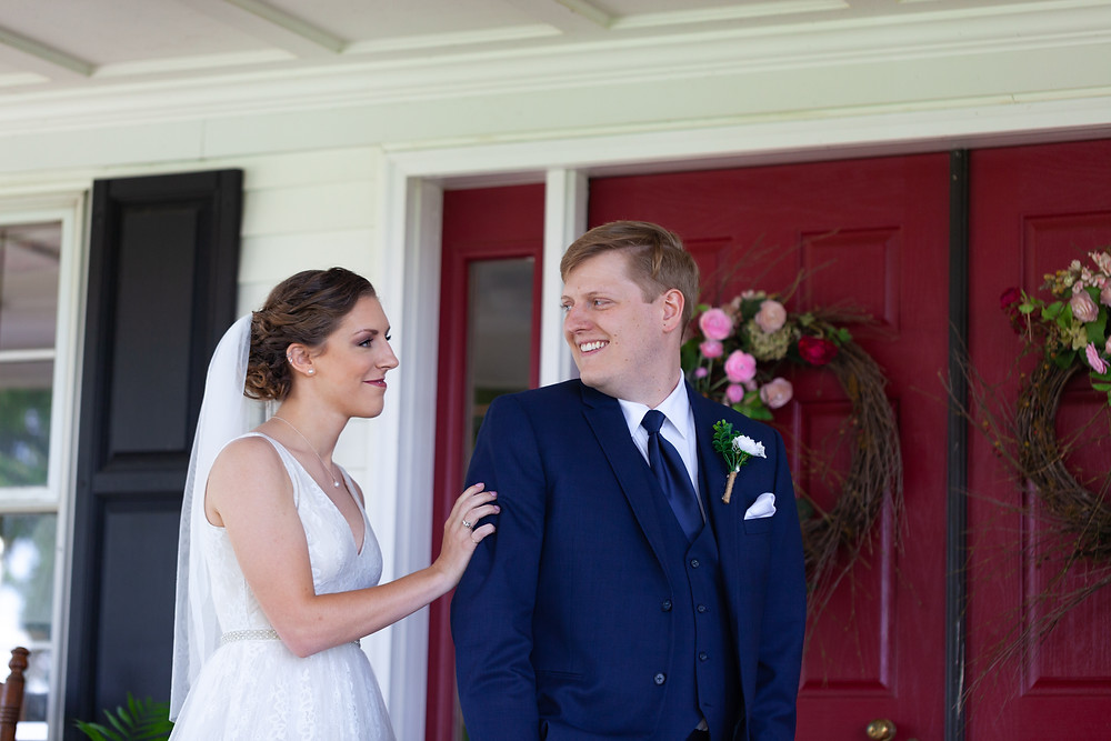 First look between bride and groom in front of red door at Lewis Family Farms