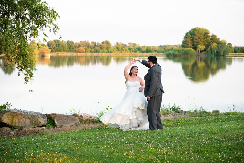 Groom spinning his bride in front of the lake at Drake's Landing Banquet Center