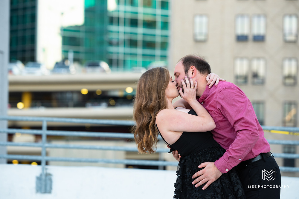 Couple kissing on parking garage roof during engagement session in Pittsburgh