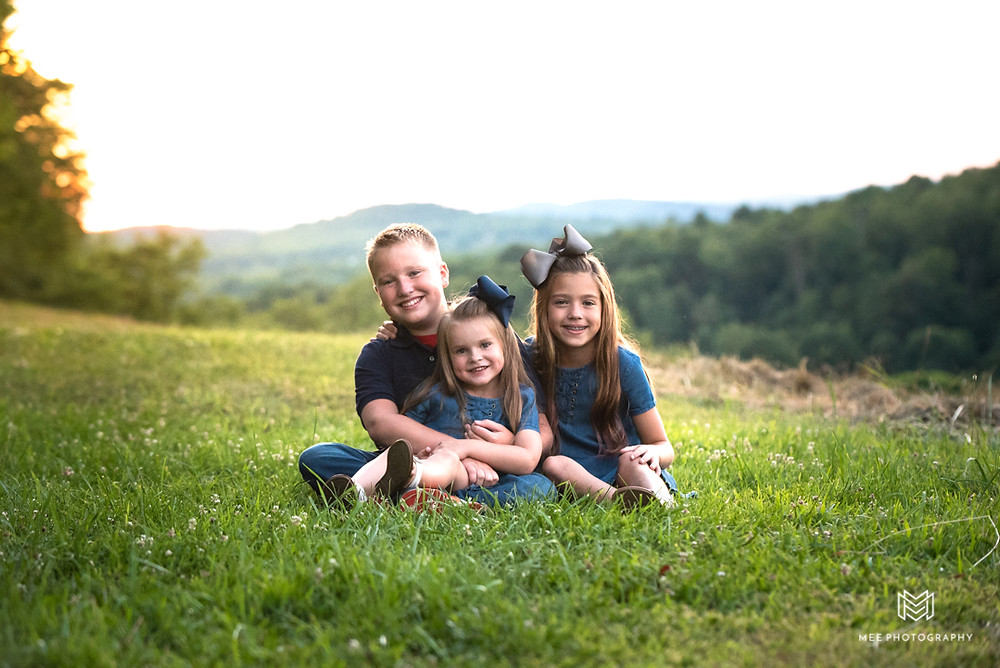 Kids posed sitting in a grassy field dressed in blue at sunset