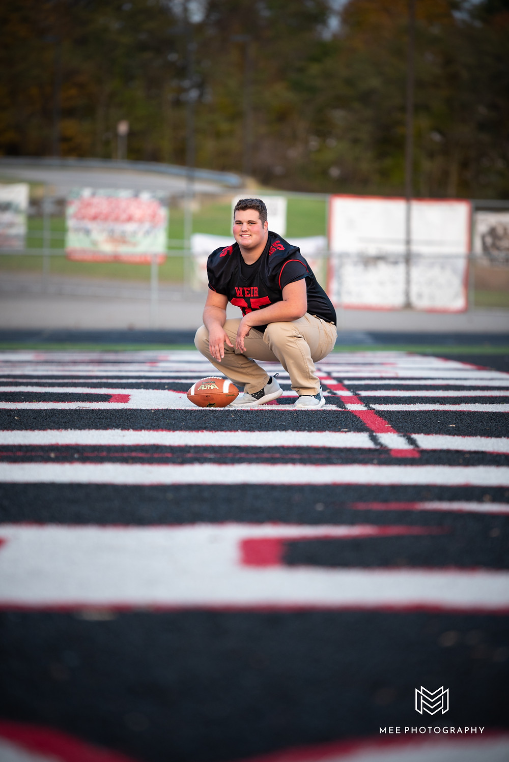 Senior guy crouching in the end zone of the football field during his senior photos at Weirton High School in West Virginia