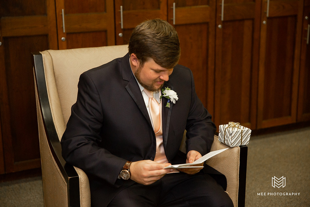 Groom opening his gift from his bride