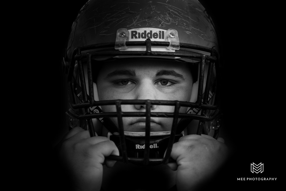Black and white senior photography of a male Weir High football player in his helmet