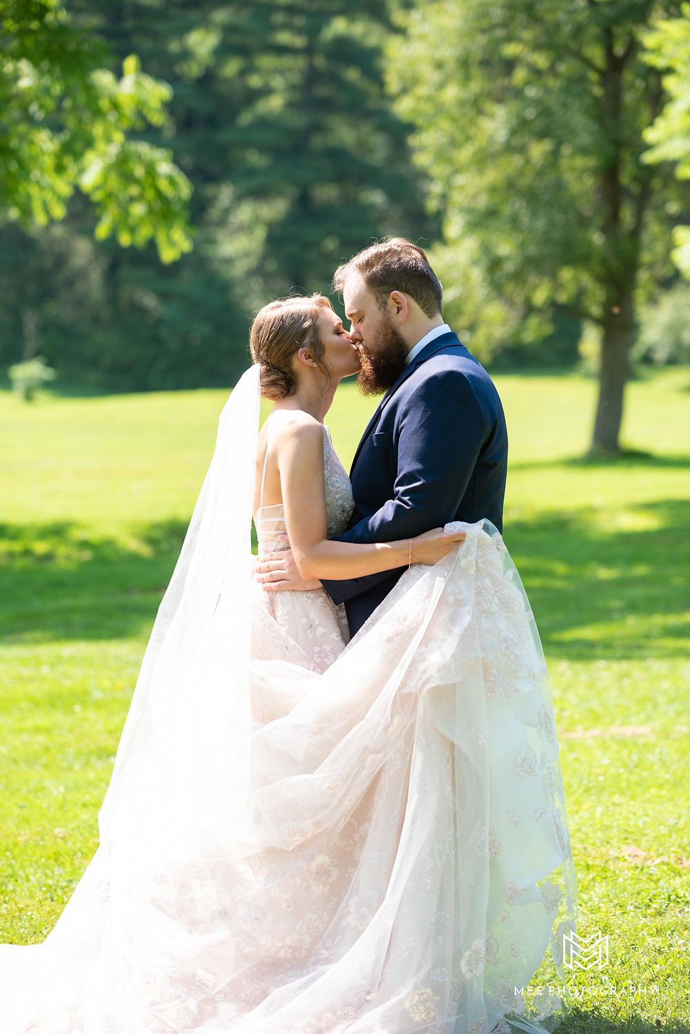 Bride and groom kissing during portraits at Chanteclaire Farm