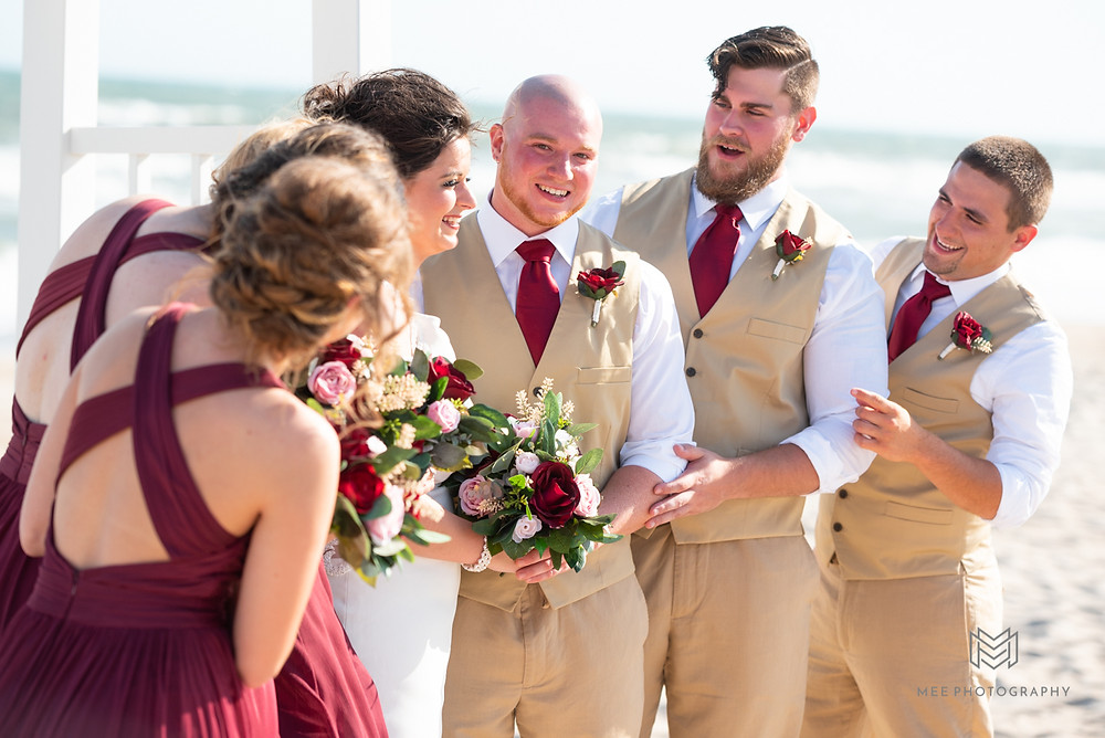 Bridal party laughing during portraits on the beach