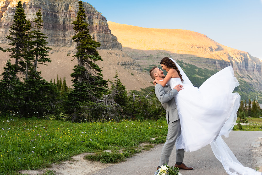 Groom lifting bride in the air with the mountains in the background at sunset in Montana