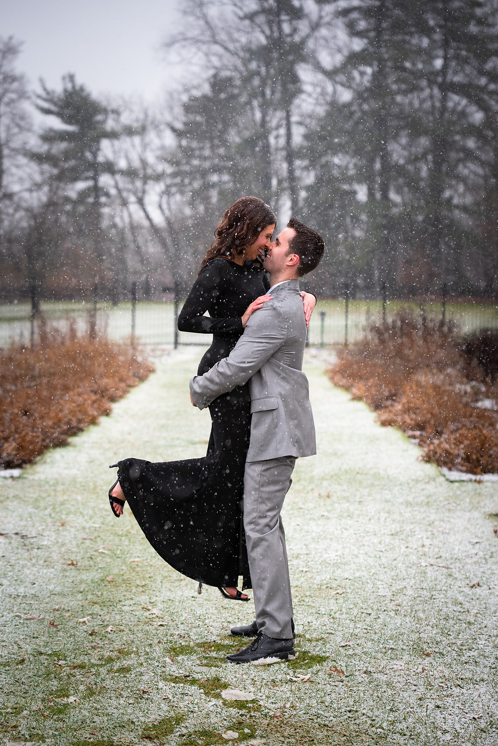 Guy holding his fiance in the snow during their winter engagement session