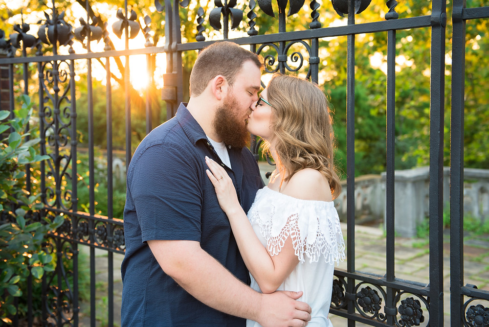 Ryan and Gingie kissing in front of a iron gate at sunset. Picture taken at Mellon Park in Pittsburgh.
