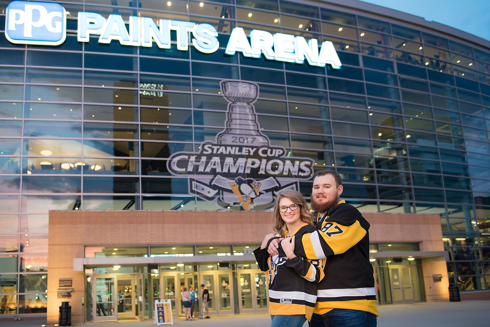 Couple wearing Pittsburgh Penguins jerseys standing in front of PPG Paints Arena in Pittsburgh, Pennsylvania.