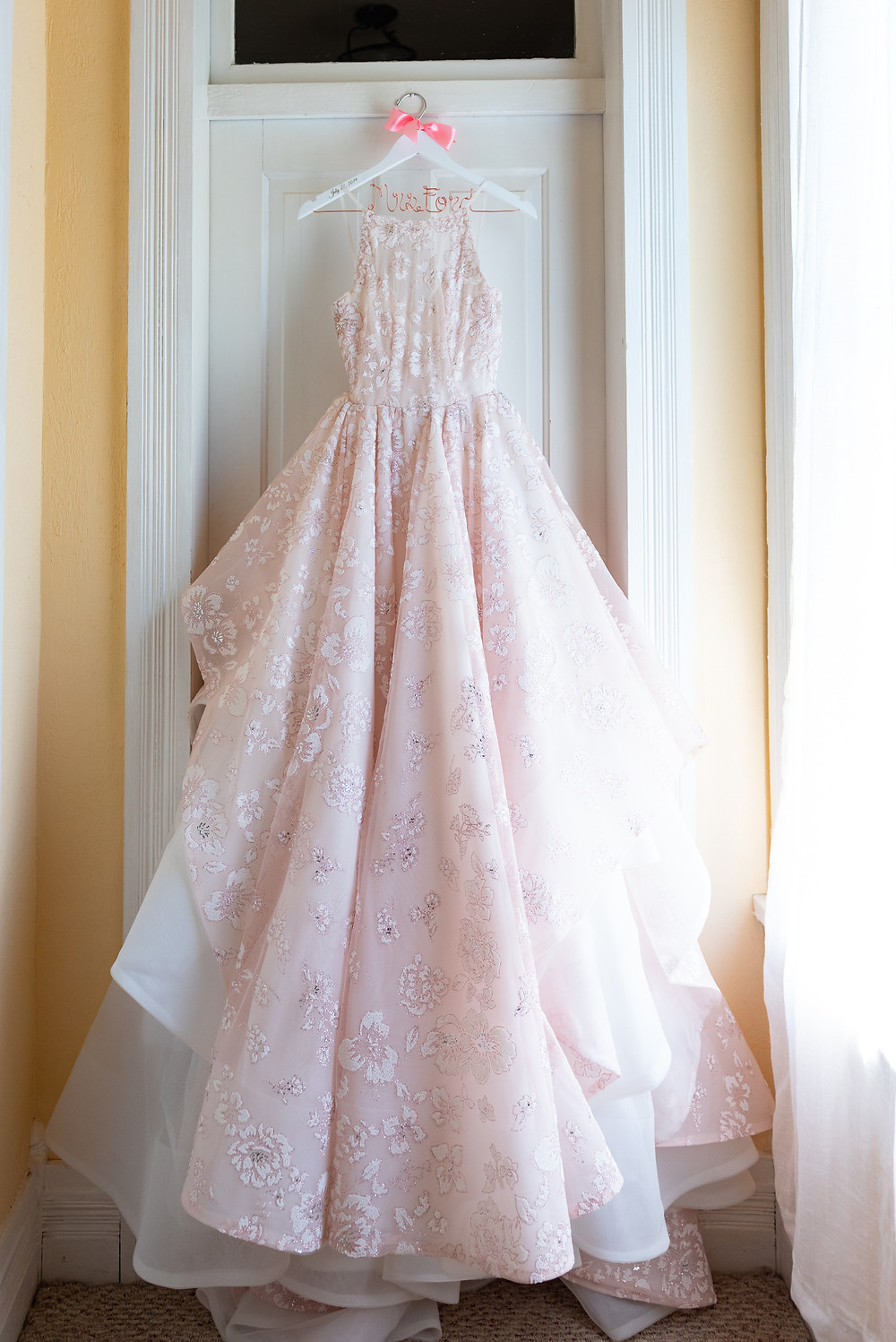 Pink Hayley Paige wedding dress hanging on a personalized hanger at Chanteclaire Farm