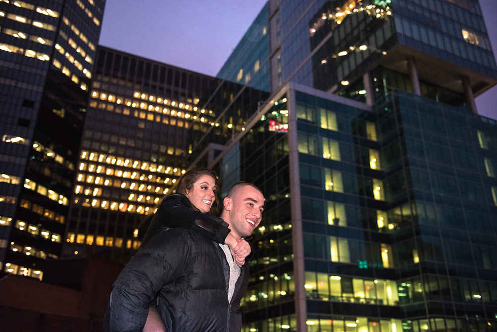 Engagement session with couple giving a piggy back ride with Pittsburgh buildings in the background