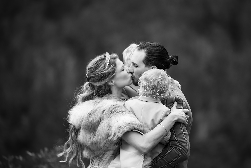 Bride and groom kissing while holding their babies