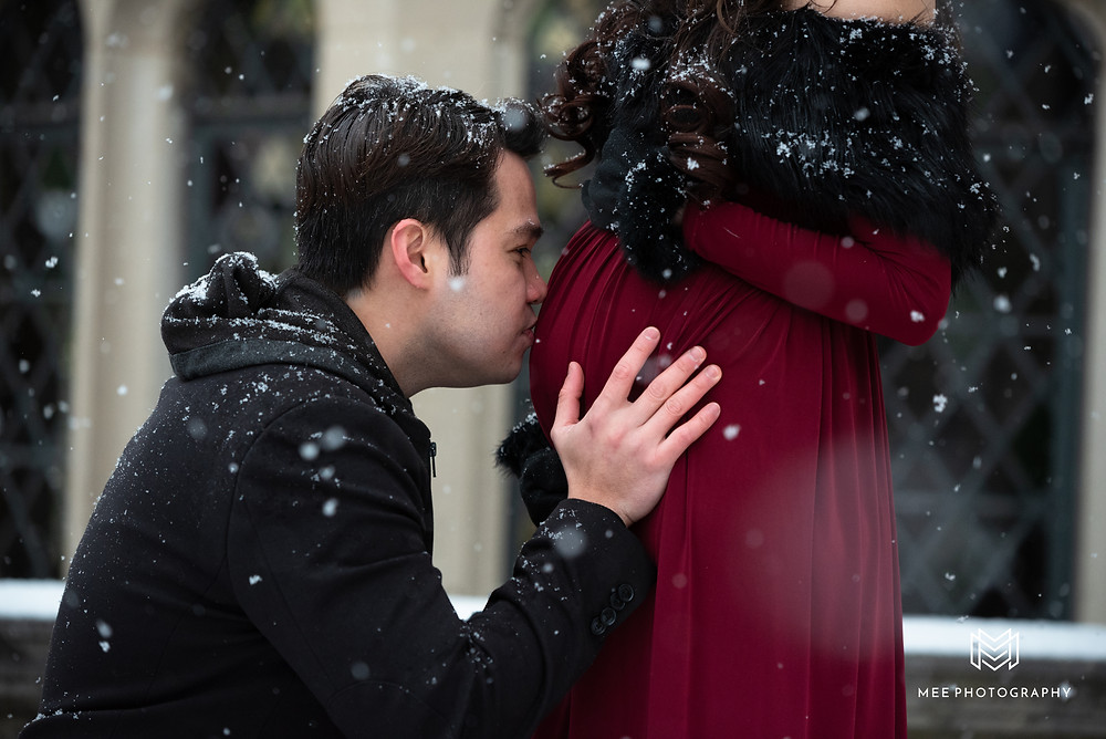 Husband kissing wife's baby bump during their maternity photos