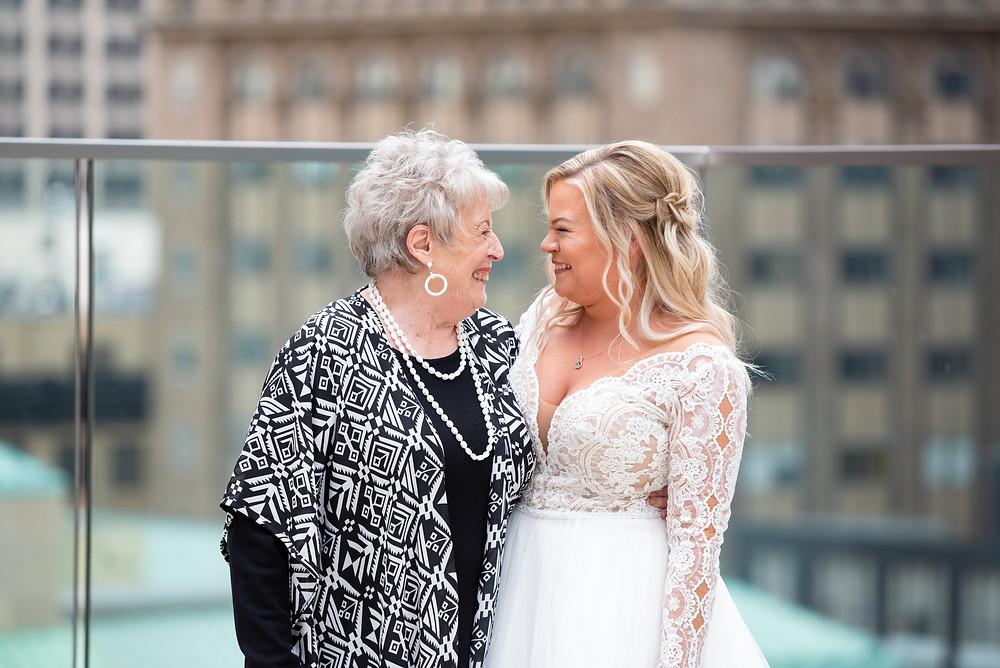 Bride laughing with her grandmother during rooftop wedding portraits
