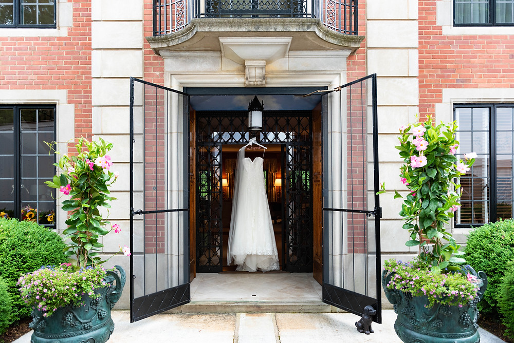 Wedding dress hanging in the doorway of a brick mansion