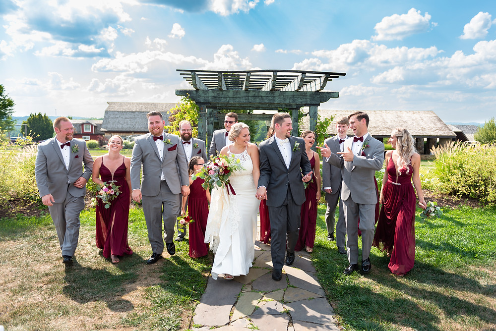 Bride and groom walking and laughing with bridal party dressed in grey and burgundy