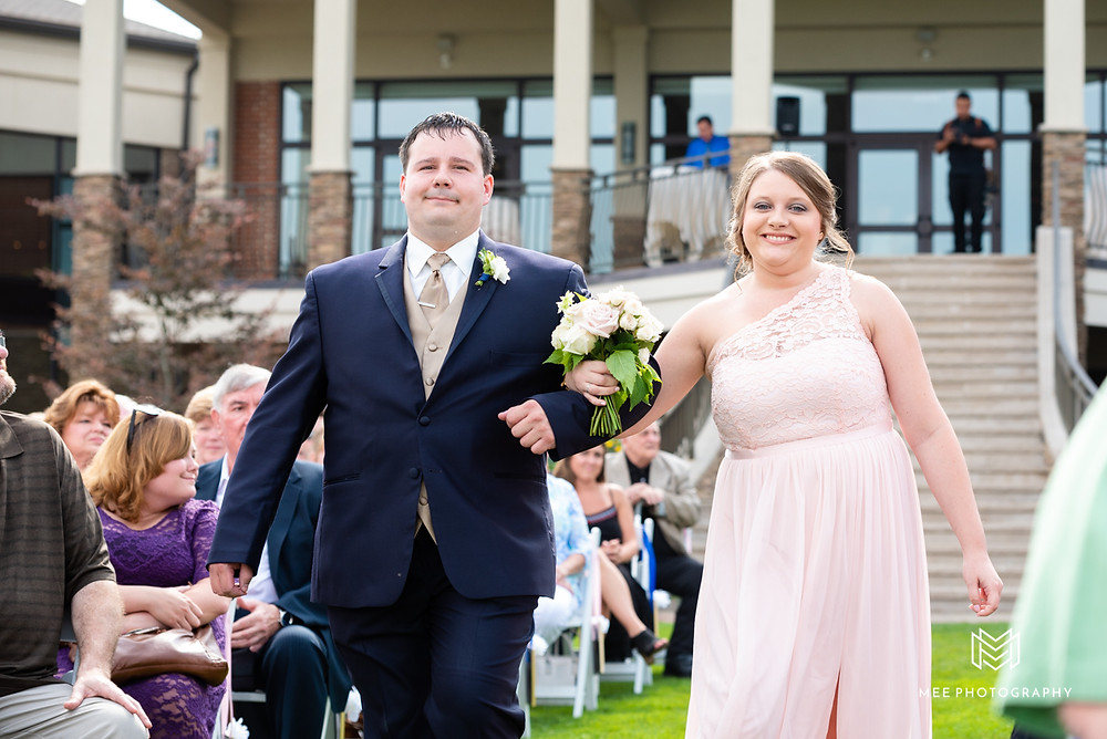 Maid of honor walking down aisle in a blush dress