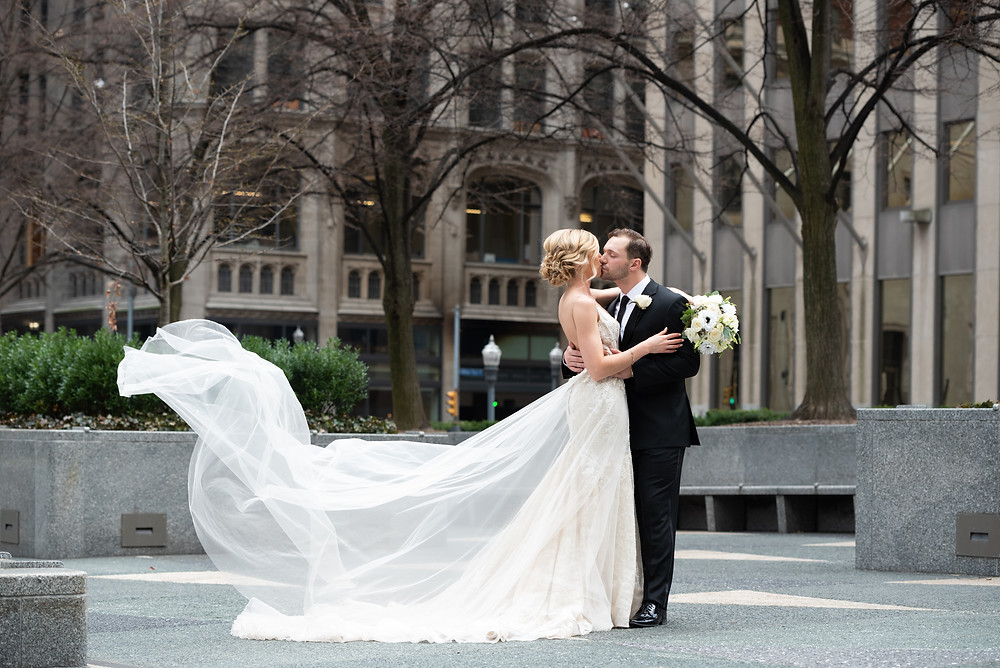 Bride's Berta overskirt blowing in the wind in Mellon Square in Pittsburgh