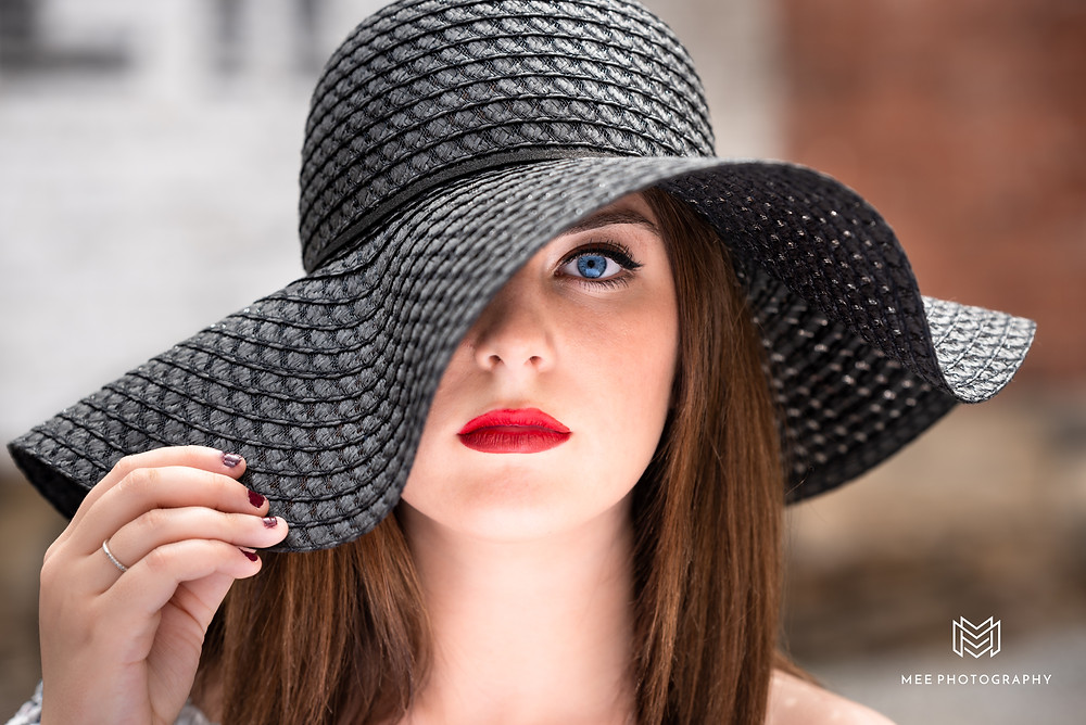 Senior girl peering out from under a black floppy hat with one eye shown