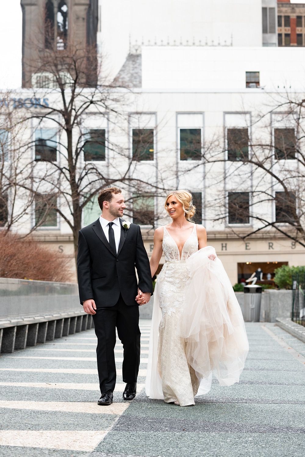 Bride and groom walking and holding hands in Mellon Square