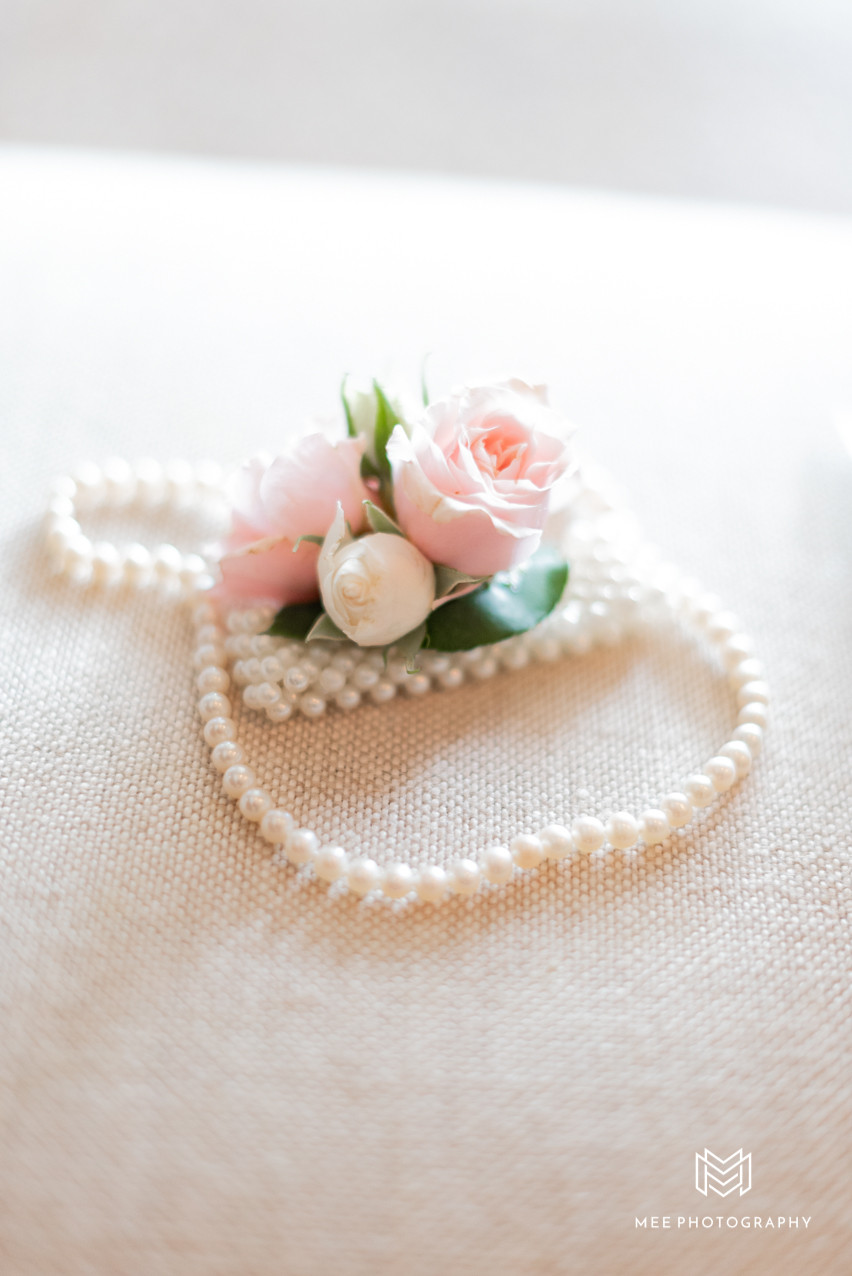 Mother of the bride's corsage and bride's pearl necklace detail shot
