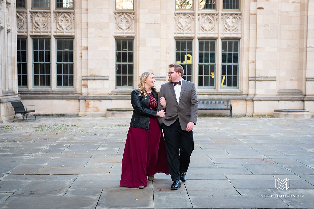 Couple strolling hand in hand at Pitt Cathedral in a dress and suit