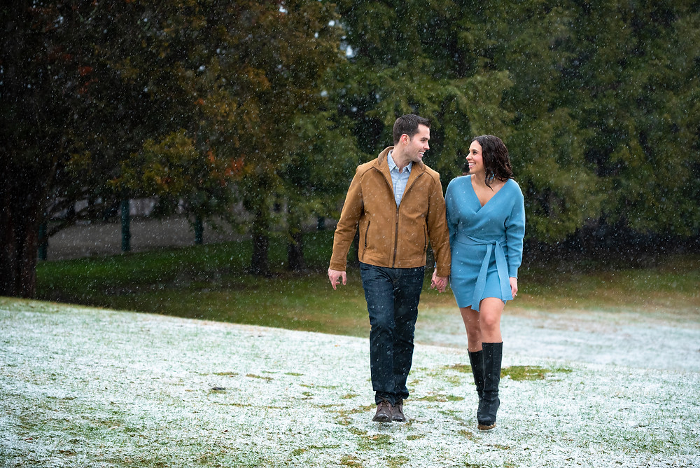 Couple walking through the snow during their engagement photos at Hartwood Acres