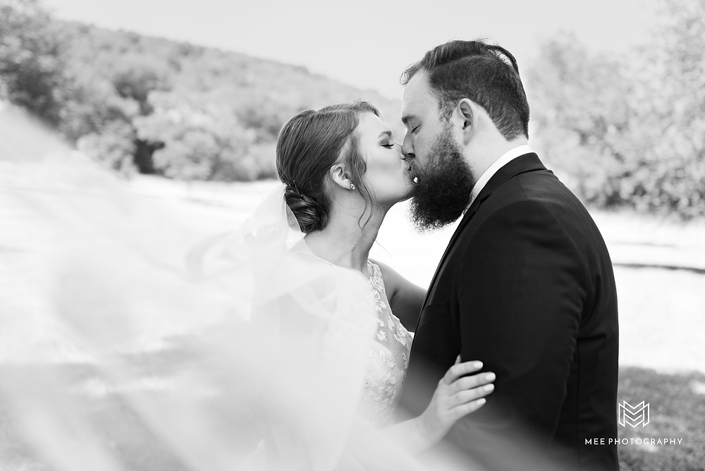 Black and white veil photo of bride and groom kissing