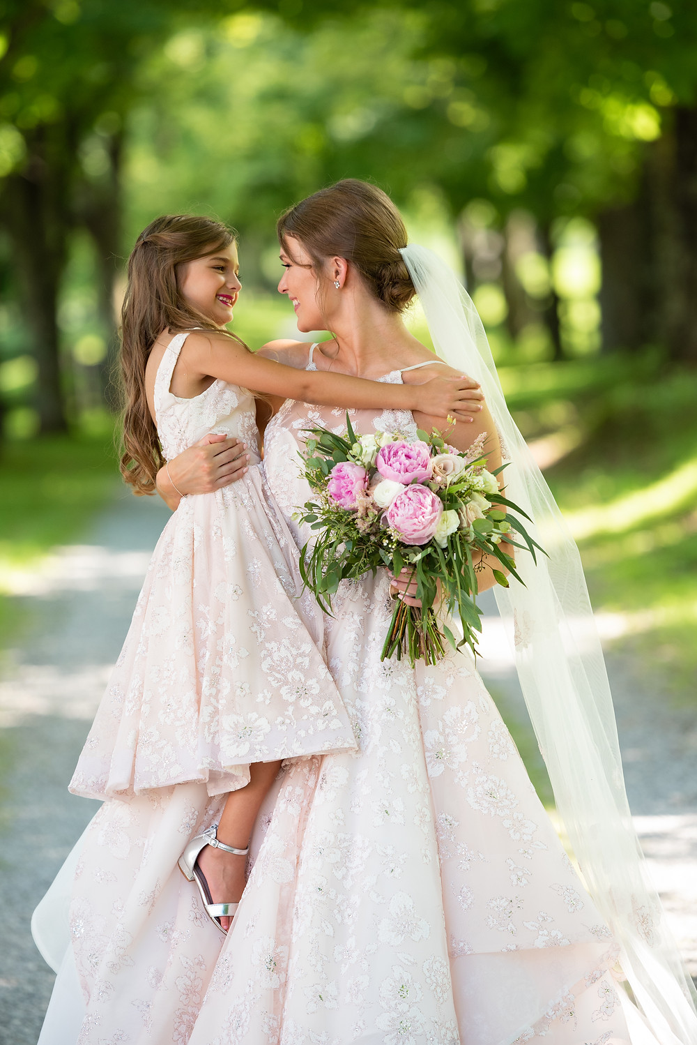 Bride and flower girl wearing matching pink Hayley Paige dresses